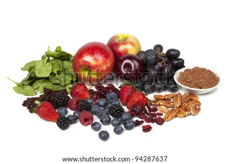 Foods rich in antioxidants, isolated on white.  Includes spinach, raisins, apples, plums, red grapes, cocoa powder, pecans, cranberries, strawberries, blueberries, raspberries and blackberries. - stock photo