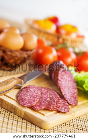 foods (tomatoes, eggs, apples, Bulgarian pepper, hazelnuts, garlic and smoked sausage on cutting board with knife) on tablecloth