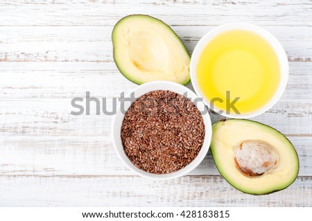 Foods with healthy fats. Sources of omega 3 - avocado, olive oil and flax seed on wooden background with copy space. Healthy food concept. Top view - stock photo