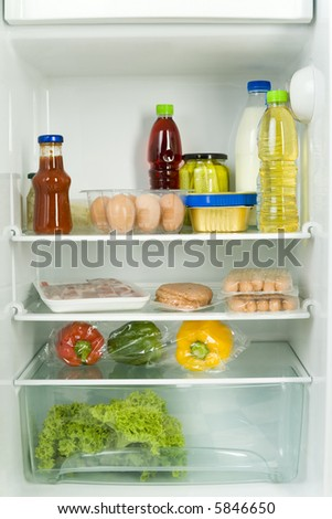 Foodstuffs in fridge. Front view. - stock photo