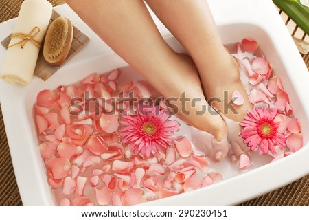 Foot bath in bowl with flower petals - stock photo