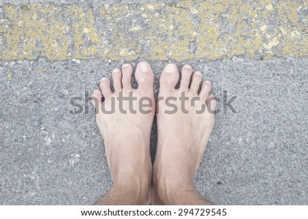 foot female on the asphalt road behind yellow line.  concept, danger or warning sign . - stock photo