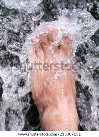foot in cold water flow - stock photo