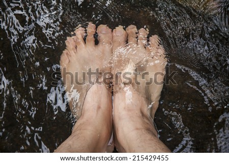 foot in cold water flow. - stock photo
