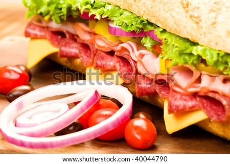 Foot-long Salami, Ham, cheese sub with lettuce, tomato, onion and peppers - stock photo