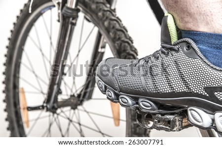 foot man in modern stylish sneakers on a bicycle pedal Male leg wear sport shoe with blue sock isolated on gray background Close up image  - stock photo