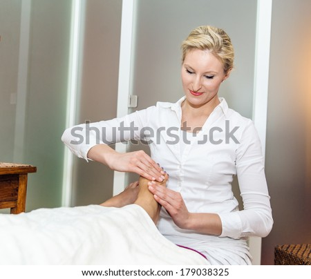 Foot massage by a therapist in a spa salon - stock photo