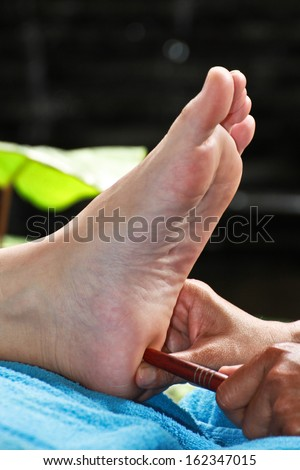 foot massage by wood stick for testis or ovary - stock photo