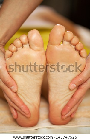 Foot massage for a woman in a luxury spa