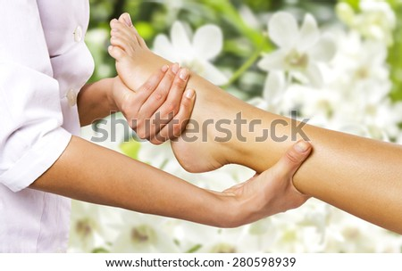 Foot massage in the spa salon in the garden. - stock photo