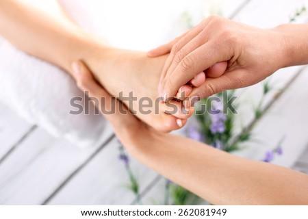 Foot massage.Masseuse massaging woman's foot. - stock photo