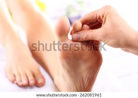 Foot massage. Masseuse massaging woman's foot. - stock photo