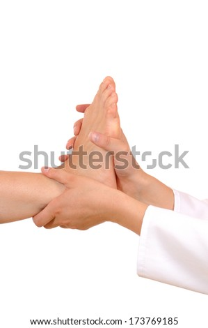 Foot massage of a young woman in front of a white background - stock photo