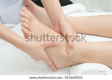 Foot massage, therapist's hands massaging female foot - stock photo