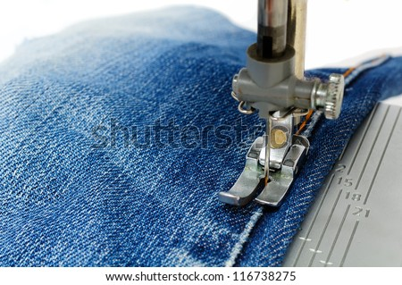 Foot of Sewing Machine on Jeans Fabric - stock photo
