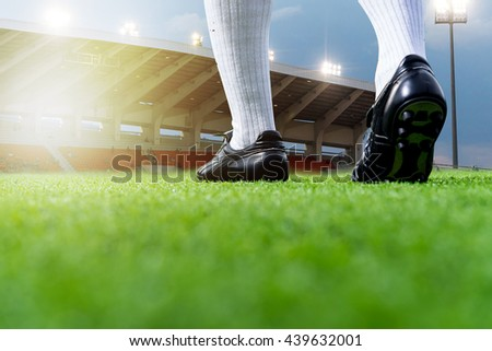 Foot of soccer player or football player walk on green grass ready to play soccer match for the winner with soccer stadium backgrounds. - stock photo