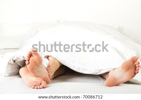 Foot of two people in the bedroom, on white background - stock photo
