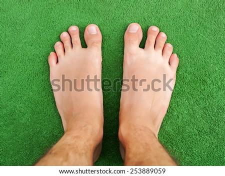 Foot on green grass - stock photo