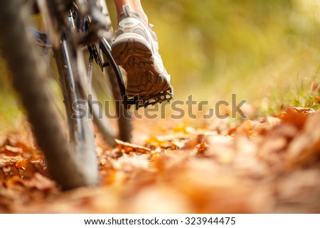 foot on pedal of bicycle in park, active summer - stock photo