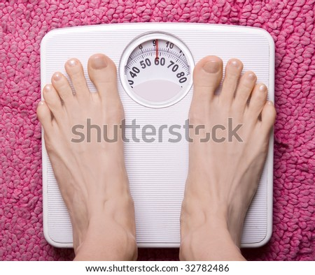 Foot placed onto bathroom scales - stock photo