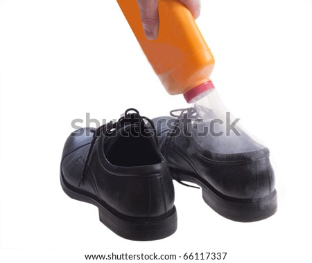 Foot powder being poured into shoe to control odor. - stock photo