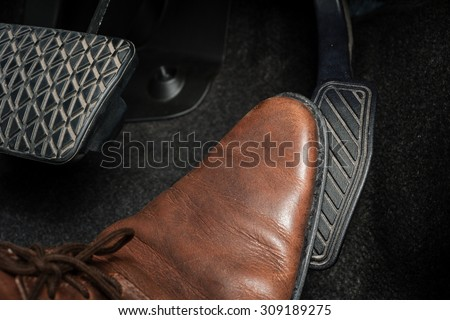 foot pressing the accelerate pedal of a car - stock photo