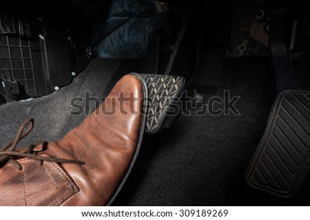 foot pressing the brake pedal of a car