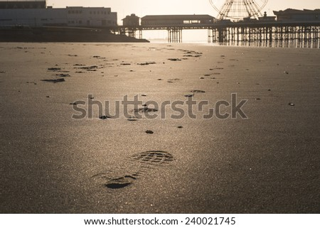 foot prints along the beach during the morning sunshine at Blackpool beach, UK - stock photo