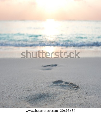 Foot prints at sand in sunrise on tropical beach - stock photo