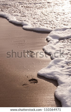 Foot prints at sand in sunset - stock photo