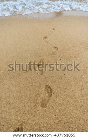 Foot prints in sand at beach - stock photo