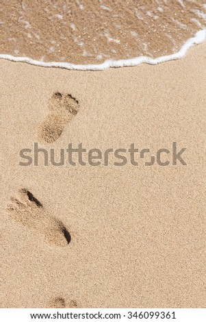 Foot prints on a sandy beach background