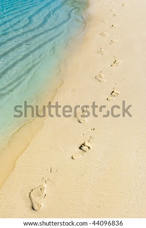 Foot steps and surf on tropical beach - abstract travel background - stock photo