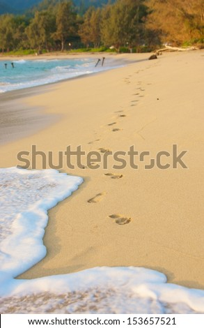 Foot steps are washed away by the surf of a rising tide on a sunset beach with trees in the background. - stock photo