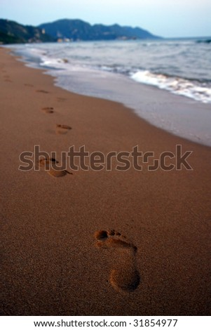 foot steps on the beach - stock photo