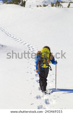 Foot steps on the snow and mountaineer progressing along during winter day - stock photo