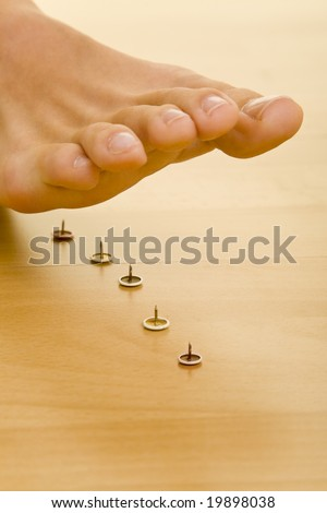 Foot walking on pins - stock photo
