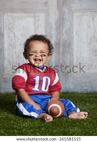 Football!  Adorable baby sitting in the grass wearing a football uniform.