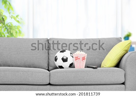 Football and a box of popcorn on a modern sofa, indoors - stock photo