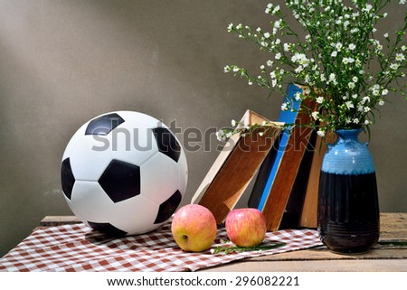 Football and Daisies on old wood. - stock photo