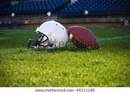 Football and helmet on a field - stock photo