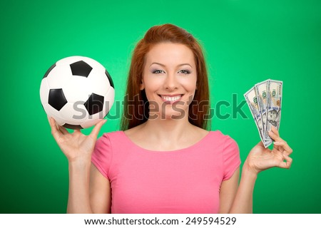 Football and money. Young attractive woman holding soccer ball and cash isolated on green background. Competition lottery gambling concept idea - stock photo