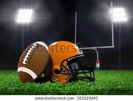 Football Ball and Helmet On Grass under Spotlights - stock photo