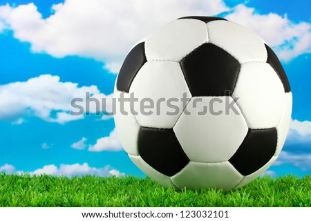 football ball on green grass, on blue sky background - stock photo