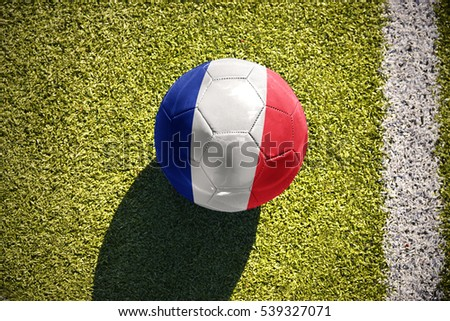 football ball with the national flag of france lies on the green field near the white line