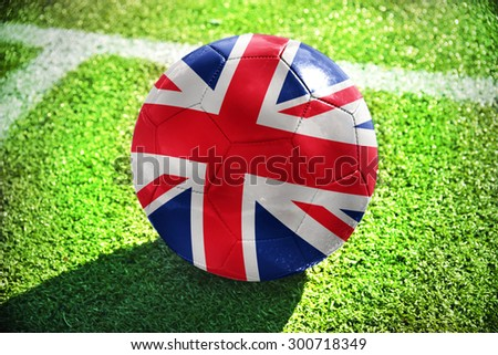 football ball with the national flag of great britain lies on the green field near the white line - stock photo