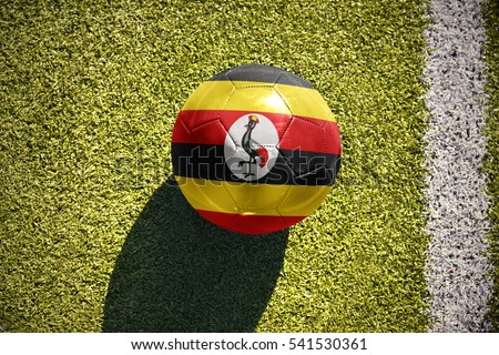 football ball with the national flag of uganda lies on the green field near the white line