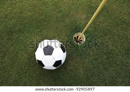 Football big ball at golf field hole - stock photo