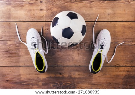 Football boots and ball laid on a wooden floor background - stock photo
