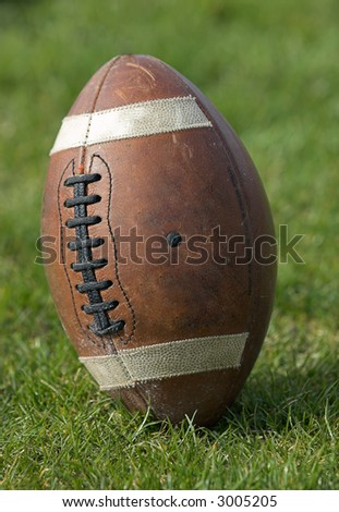 Football - closeup of football standing upright on the playing field. - stock photo